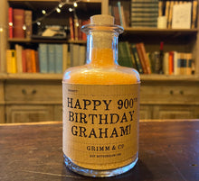 Load image into Gallery viewer, Image of a glass potion bottle filled with orange bath salts. The bottle label reads: Happy 900th Birthday Graham!