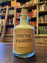 Load image into Gallery viewer, Image of a glass potion bottle filled with pale green bath salts. The bottle label reads: You've Passed!
