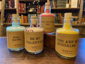 Image of four personalised potion bottles, otherwise known as scented bath salts in a glass bottle with cork and a brown kraft label. From left to right - Blue Potion label reads: Soul Mates. Pink and rose petal  Potion label reads: Be My Valentine. Red Potion label reads: Will You Marry Me? Yellow Potion label reads: You Are My Sunshine.