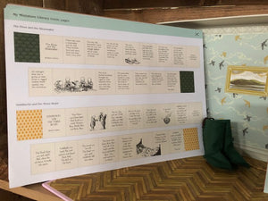 Image showing the details of an inside page of My Miniature Library with two stories (The Elves and The Shoemaker and Goldilocks and The Three Bears). The page rests against the inside of the box, which is decorated to look like a library space. The image also contains a pair of pixie boots not included within the kit.