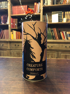 Image of Creature Comforts, otherwise known as clotted cream shortbread biscuits in a tube. Tube is a design of kraft paper printed with a silhouette of woodland trees and creatures.