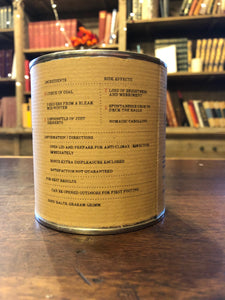 Image shows the back of a tin of Festive Disappointment with kraft paper label of faux ingredients and side effects
