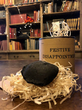 Load image into Gallery viewer, Image shows a tin of Festive Disappointment with kraft paper label, lid is open showing wood wool shreds and a lump of black coal