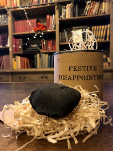 Image shows a tin of Festive Disappointment with kraft paper label, lid is open showing wood wool shreds and a lump of black coal