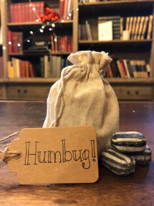 Image shows a drawstring pouch of humbugs, with the kraft label  and a pile of three humbug sweets in front.