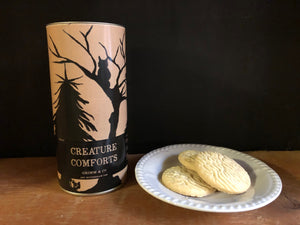 Image of Creature Comforts, otherwise known as clotted cream shortbread biscuits in a tube. Image shows tube with some biscuits sat on a plate. Tube is a design of kraft paper printed with a silhouette of woodland trees and creatures