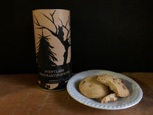 Load image into Gallery viewer, Image of Pointless Procrastinations, otherwise known as chocolate chip biscuits in a tube. Image shows tube with some biscuits sat on a plate. Tube is a design of kraft paper printed with a silhouette of woodland trees and creatures.