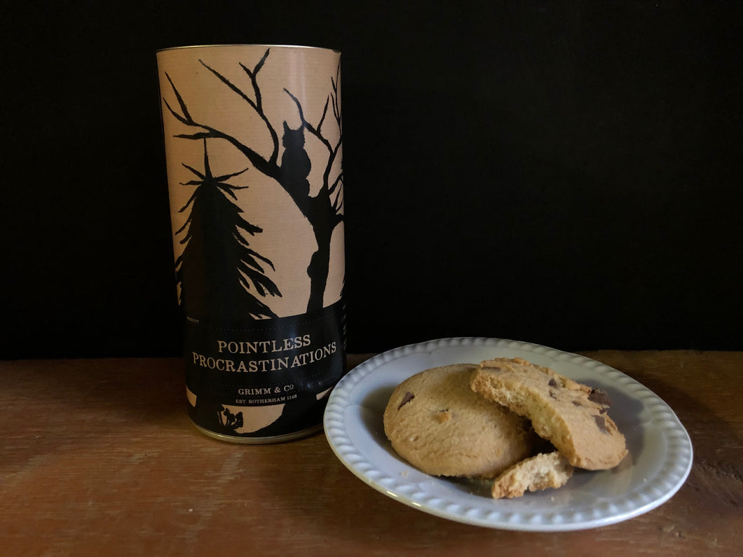 Image of Pointless Procrastinations, otherwise known as chocolate chip biscuits in a tube. Image shows tube with some biscuits sat on a plate. Tube is a design of kraft paper printed with a silhouette of woodland trees and creatures.