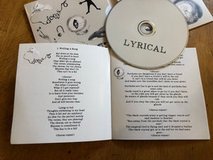 Image shows the Lyrical album CD laid out side the album cover with the lyric book open to show the first two songs and their lyrics.