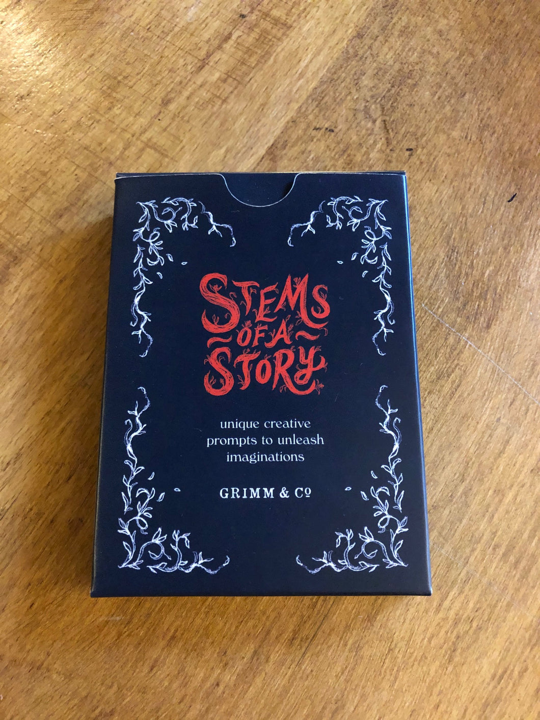 Image showing the front of the cardboard box for the card game Stems of a Story, created by children and young people during workshops at Grimm and Co.