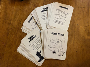 Image shows the Stems of a Story game cards in small piles of their categories: mealtime, going to bed, family& friends, journeys, and leisure activities.
