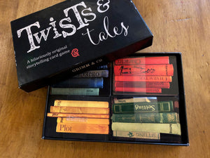 Image of the Twists & Tales box with the lid partly removed, showing the card categories within. There are four sets of cards decorated to look like books on a shelf, and they are colour coordinated. Blue cards for Objects, red cards for Characters, green cards for Settings, and yellow cards for Plot.