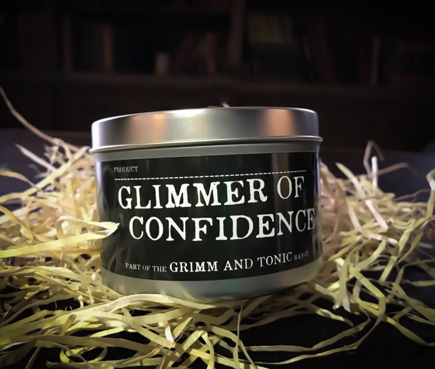Image of the Glimmer of Confidence, a tinned candle with slip lid in the Grimm & Tonic range with a black label and white text.