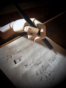 Image of a matte black Dip Wand in a wooden mannequin hand poised above paper with cursive writing. Dip Wand is a wooden dip pen with nib for use with writing or drawing inks