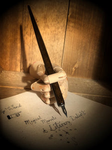 Image of a Dip Wand in a wooden mannequin hand poised above paper with cursive writing. Dip Wand is a wooden dip pen with nib for use with writing or drawing inks