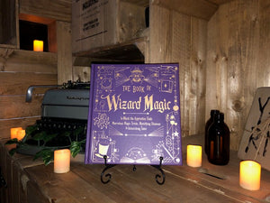 Image of the front cover for The Book Of Wizard Magic, written by Janice Eaton Kilby. The lighting of the image shows off the reflective lettering on the cover. Displayed on a book stand with candles..