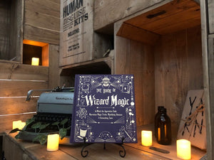 A further back image showing the front cover for The Book Of Wizard Magic, written by Janice Eaton Kilby. Displayed on a book stand with candles.