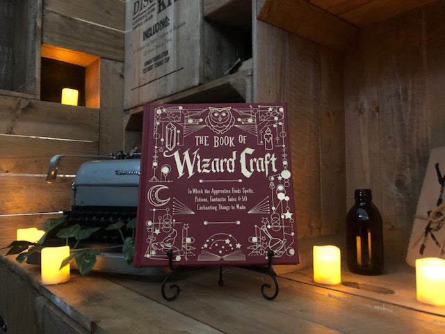 Image shows the front cover of The Book Of Wizard Craft, written by Janice Eaton Kilby. Displayed on a book stand with candles.