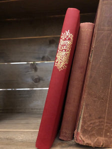 Image of A Christmas Carol by Charles Dickens. The book is stood on a bookshelf to show gold detailing on the spine. It rests against two other decorative hardback books.