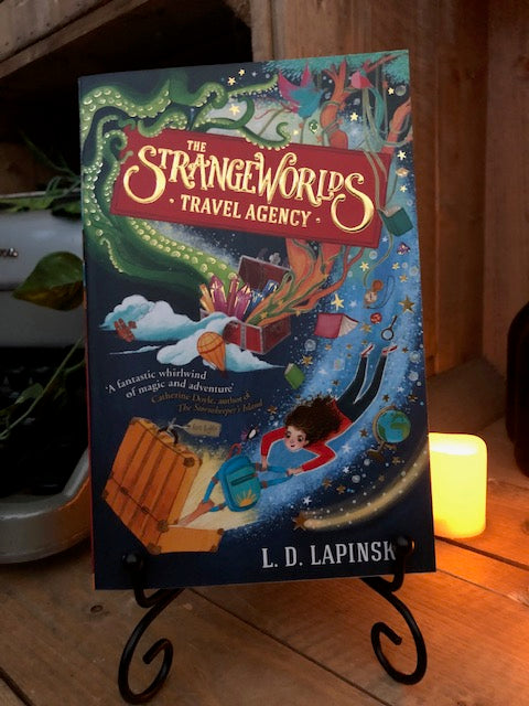Image of the front cover of the paperback book The Strangeworlds Travel Agency, written by L.D. Lapinski. Displayed on a book stand with candles.