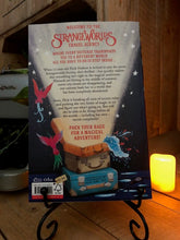 Load image into Gallery viewer, Image of the back cover of the paperback book The Strangeworlds Travel Agency, written by L.D. Lapinski. Displayed on a book stand with candles.