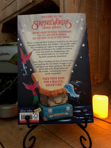Image of the back cover of the paperback book The Strangeworlds Travel Agency, written by L.D. Lapinski. Displayed on a book stand with candles.