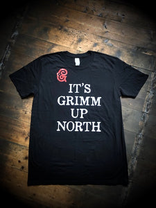 Close up image of the larger print on the Human Disguise t-shirt made from black cotton and printed with the slogan 'IT'S GRIMM UP NORTH' in white ink and the Grimm & Co red 'G' monogram at the top left of the slogan.