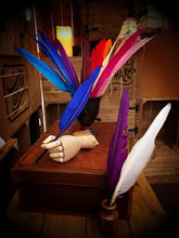 Load image into Gallery viewer, Image of several Biro Quills, coloured feathers with biro pens attached, held in wooden mannequin hands