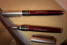 Load image into Gallery viewer, Image of two Fancy Word Wands, otherwise known as a roller-ball, black ink pen, with chrome tip and lid, black rubber grip, and metallic red body, with 'Grimm & Co' printed in silver lettering in the middle. One is displayed with the lid on, and one with the lid removed to show the nib.