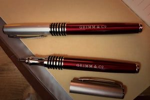 Image of two Fancy Word Wands, otherwise known as a roller-ball, black ink pen, with chrome tip and lid, black rubber grip, and metallic red body, with 'Grimm & Co' printed in silver lettering in the middle. One is displayed with the lid on, and one with the lid removed to show the nib.