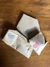 Load image into Gallery viewer, Image shows the wrapped mystery options of the Lucky or Unlucky Dip, each item is wrapped in kraft paper and stamped with the Grimm & Co 'G' monogram