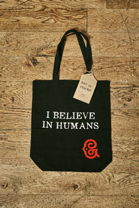 Image of black cotton tote book bag with white printed slogan on front saying 'I BELIEVE IN HUMANS ' with the red Grimm & Co 'G' monogram in the bottom right corner