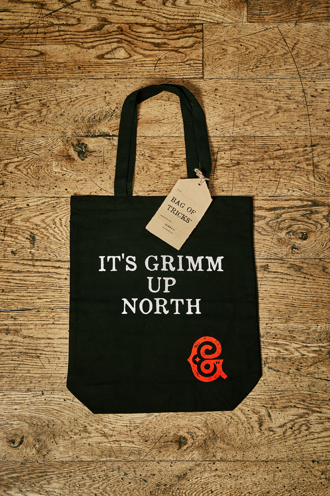 Image of black cotton tote book bag with white printed slogan on front saying 'IT'S GRIMM UP NORTH' with the red Grimm & Co 'G' monogram in the bottom right corner