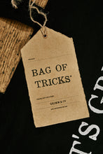 Load image into Gallery viewer, Close up of kraft paper label of black cotton tote book bag called Bag of Tricks