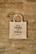 Load image into Gallery viewer, Image of a jute tote bag with slogan 'It's Grimm Up North' printed on the front