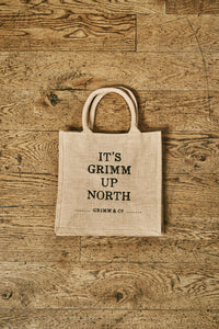 Image of a jute tote bag with slogan 'It's Grimm Up North' printed on the front