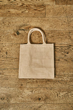 Load image into Gallery viewer, Image of the back of a jute tote bag