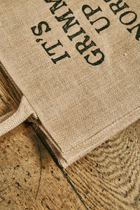Close up image of the jute tote bag showing the printed slogan 'It's Grimm Up North' in capital letters
