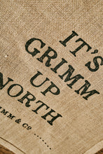 Load image into Gallery viewer, Close up image of the jute tote bag showing the printed slogan 'It's Grimm Up North' in capital letters