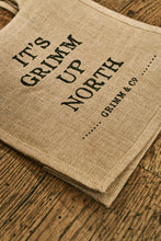 Load image into Gallery viewer, Angled image of a jute tote bag with slogan 'It's Grimm Up North' printed on the front