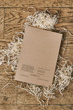 Load image into Gallery viewer, Image of the back cover of the How to Avoid Humans note book. Notebook is made from kraft card with white pages.