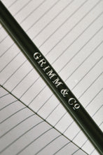 Load image into Gallery viewer, Close up details of lettering on a Word Wand, otherwise known as a black pencil with a black eraser at the top. The silver lettering in the image reads 'Grimm & Co.'