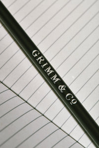 Close up details of lettering on one side of a Word Wand, otherwise known as a black pencil with a black eraser at the top. The silver lettering in the image reads 'Grimm & Co.'