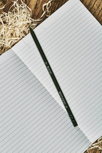 Image of a Word Wand, otherwise known as a black pencil with silver printed writing along the length and a black eraser at the top. The lettering on this side of the pencil reads 'Mistakes' with an arrow pointing towards the eraser, and 'Magic' with an arrow pointing towards the lead. The Word Wand rests on a lined kraft note book.