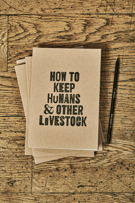 Image shows a few kraft card notebooks in a pile with the top one displaying the slogan HOW TO KEEP HUMANS & OTHER LIVESTOCK'. Notebooks are shown with a Word Wand pencil.