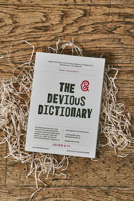 Image of the front cover of The Devious Dictionary, a white paperback book. The title is written in large black letters in the center with a red Grimm & Co monogram. Charity information is written below, and a sentence stating the writings are original contributions from  storymakers at Grimm and Co. is written above.