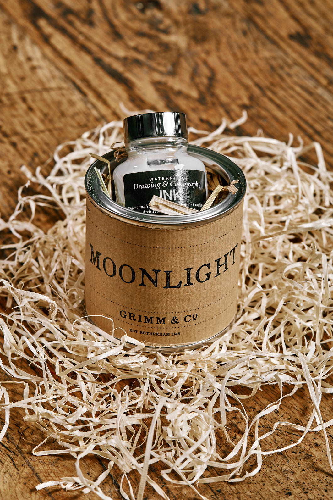 Image of a tin of Moonlight. A silver drawing or writing ink nestled in wood wool inside the tin and wrapped with a kraft paper label.