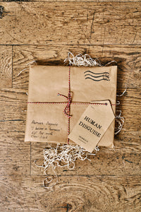 Image shows how the Human Disguises are wrapped when ordered in kraft brown paper and tied up with bakers twine and a kraft paper label. Parcel resembles an envelope with Grimm & Co stamp in top right corner