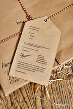 Load image into Gallery viewer, Image shows how the Human Disguises are wrapped when ordered in kraft brown paper and tied up with bakers twine and a kraft paper label showing the size of the item.