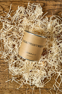 Image of a tin of Disappointment with a kraft label shown sat in a nest of wood wool.